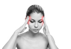 Een jonge vrouw die aan pijn in het hoofd lijden stock afbeelding