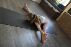 Een jonge vrouw die Ashtanga-yoga uitoefenen royalty-vrije stock afbeelding