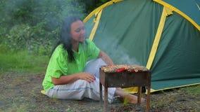 Een jonge vrouw die in een bos op de achtergrond van een tent zit bereidt een barbecue op de grill voor algemeen plan stock videobeelden