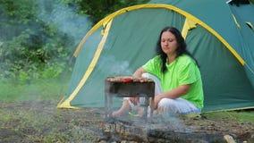Een jonge vrouw die in een bos op de achtergrond van een tent zit bereidt een barbecue op de grill voor algemeen plan stock footage
