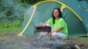 Een jonge vrouw die in een bos op de achtergrond van een tent zit, bereidt diner op haar koperslager voor algemeen plan stock videobeelden