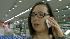 Een jonge vrouw die een opslag bezoeken stock video