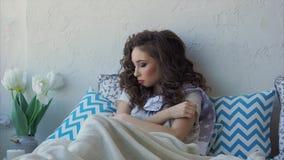 Een jonge vrouw die onlangs is ontwaakt, ligt op een bed, dat op een hoofdkussen leunt stock video