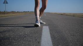 Een jonge vrouw die op de weg lopen stock video