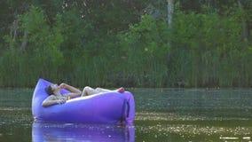 Een jonge vrouw die op een luchtbed liggen neemt het zonnebaden en zeilen langs de rivier stock footage