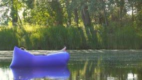 Een jonge vrouw die op een luchtbed liggen neemt het zonnebaden en zeilen langs de rivier stock videobeelden