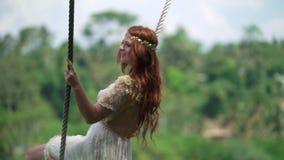 Een jonge vrouw die op een schommeling in Bali over een klip slingeren Roodharige bruid bij haar dag van de huwelijksviering stock videobeelden