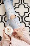 Een jonge vrouw die verontruste jeans dragen die op houten vloer op een dekentapijt thuis zitten en een kop van koffie in handen  Royalty-vrije Stock Foto