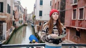 Een jonge vrouw die zich op de kleine brug boven het waterkanaal bevinden en de kaart bekijken om de manier te vinden stock footage