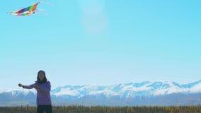 Een jonge vrouw die zijn vlieger op een gebied met bergen en gletsjers vliegen stock videobeelden