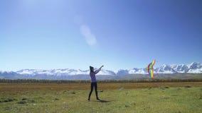 Een jonge vrouw die zijn vlieger op een gebied met bergen en gletsjers vliegen stock footage