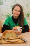 Een jonge vrouw drinkt thee in de keuken Stock Foto