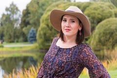 Een jonge vrouw in een donkere kleding en een witte hoed Stock Fotografie