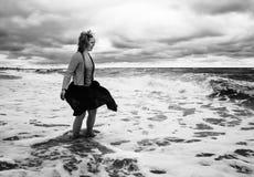 Een jonge vrouw in een golvende rok bevindt zich onder het stormachtige overzees w stock foto's