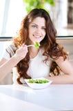 Een jonge vrouw in een koffie met een coffe met salade Stock Afbeeldingen