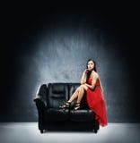 Een jonge vrouw in een rode kleding op een zwarte leerbank Stock Fotografie