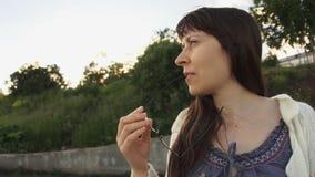 Een jonge vrouw in een wit gebreid peinzend jasje knagend aan de rand van glazen stock videobeelden