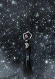 Een jonge vrouw in een zwarte kleding op een sneeuwachtergrond Stock Afbeelding