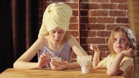 Een jonge vrouw en een klein meisje eten yoghurt bij Ontbijt stock footage