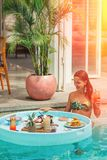 Een jonge vrouw gaat Ontbijt hebben terwijl in de pool tint verlichting stock fotografie