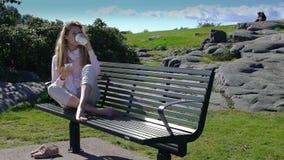 Een jonge vrouw gebruikt een smartphone en drinkt koffie op bank in park Langzame Motie stock footage