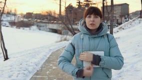 Een jonge vrouw gebruikt in openlucht een digitale tablet in de winter stock footage