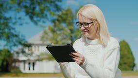Een jonge vrouw gebruikt een tablet Zit op de achtergrond van zijn huis Een typisch huis in de voorsteden in de V.S. stock foto