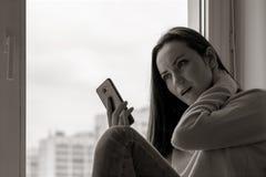 Een jonge vrouw is gedeprimeerd op een vensterbank dichtbij het venster van het huis, zwart-wit close-up, stock foto's