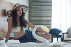 Een jonge vrouw in een geel badpak en een strohoed zit op een bed in een hotelruimte stock afbeeldingen