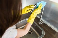 Een jonge vrouw in gele handschoenen wast kraan met een spons in de gootsteen De huis professionele schoonmakende dienst royalty-vrije stock afbeeldingen