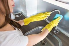 Een jonge vrouw in gele handschoenen wast kraan met een spons in de gootsteen De huis professionele schoonmakende dienst royalty-vrije stock foto