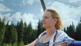 Een jonge vrouw geniet van een lift op de lift, bekijkt rond de mooie bergen en het bos stock footage