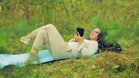 Een jonge vrouw in glazen ligt op het gras in het park en communiceert in een boodschapper op een tablet stock videobeelden