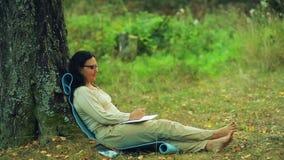 Een jonge vrouw in glazen zit blootvoets onder een boom in het park en trekt een potlood in een notitieboekje stock footage