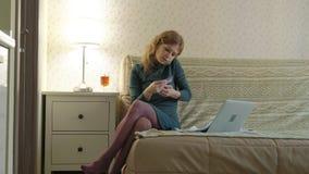Een jonge vrouw in een groene kleding zit op een bank met laptop, gebruikt een telefoon en een plastic kaart, de werken, studies stock videobeelden