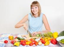 Een jonge vrouw hakt salade royalty-vrije stock afbeeldingen