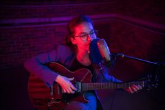 Een jonge vrouw het spelen gitaar en het zingen door mic in T.L.-verlichting stock afbeelding
