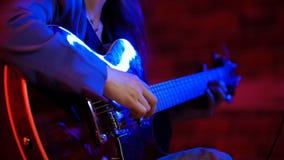Een jonge vrouw het spelen gitaar in T.L.-verlichting royalty-vrije stock fotografie