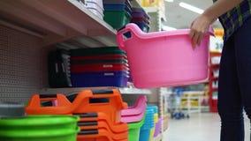 Een jonge vrouw kiest en koopt een groot bassin in een supermarkt stock footage