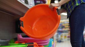 Een jonge vrouw kiest en koopt een groot bassin in een supermarkt stock videobeelden