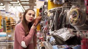 Een jonge vrouw kiest een hoofdkussen voor een auto in een supermarkt stock videobeelden