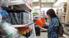 Een jonge vrouw kiest een kleine oranje container in een de bouwsupermarkt