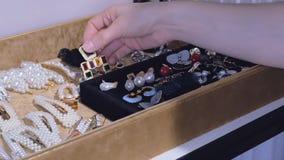 Een jonge vrouw kiest oorringen van haar inzameling manierjuwelen, mooie toebehoren voor elke dag stock video