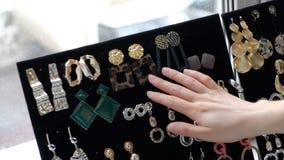 Een jonge vrouw kiest oorringen van haar inzameling manierjuwelen, mooie toebehoren voor elke dag Langzame Motie stock footage