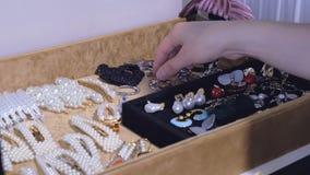 Een jonge vrouw kiest oorringen van haar inzameling manierjuwelen, mooie toebehoren voor elke dag stock footage