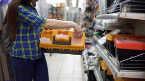Een jonge vrouw kiest een plastic hulpmiddeldoos in de opslag