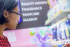 Een jonge vrouw kiest schoonheidsmiddelen bij een opslag stock fotografie