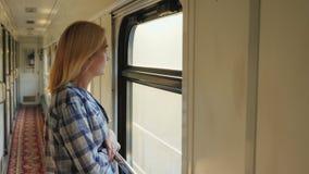 Een jonge vrouw kijkt uit het treinvenster Het is in de gang, beweegt de trein snelle Dromen en reizen stock videobeelden