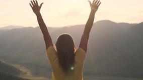 Een jonge vrouw komt aan de rand van een klip en heft omhoog haar handen voor de hoge rotsachtige bergen tijdens zonsondergang op stock videobeelden