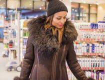 Een jonge vrouw koopt bij een supermarkt stock foto